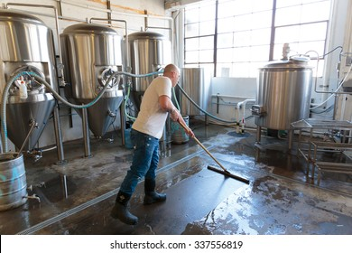 EUGENE, OR - NOVEMBER 4, 2015: Brewery owner Brandon Woodruff cleaning the floor at the startup craft brewery Mancave Brewing.