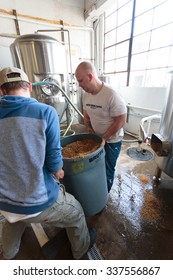 EUGENE, OR - NOVEMBER 4, 2015: Brewery co-owners Brandon Woodruff and Wes Gunderson work together to create the award-winning Exalted IPA at the startup craft brewery Mancave Brewing.