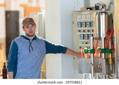 EUGENE, OR - NOVEMBER 4, 2015: Brewery co-owner Wes Gunderson controlling the temperature of a mashing machine at the startup craft brewery Mancave Brewing.