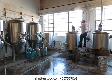 EUGENE, OR - NOVEMBER 4, 2015: Commercial brewery owner Brandon Woodruff mashing Exalted IPA at the startup craft brewery Mancave Brewing.