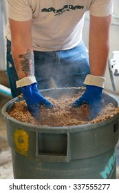 EUGENE, OR - NOVEMBER 4, 2015: Head brewmaster and brewery owner Brandon Woodruff examines a bucket of grain used for brewing beer commercially at the startup craft brewery Mancave Brewing.