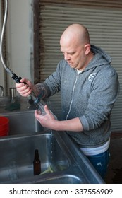 EUGENE, OR - NOVEMBER 4, 2015: Head brewmaster Brandon Woodruff washing glasses for a beer tasting at the startup craft brewery Mancave Brewing.
