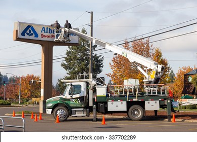 EUGENE, OR - NOVEMBER 4, 2015: Two workers installing a new sign at an Albertsons location at Oakway Center.