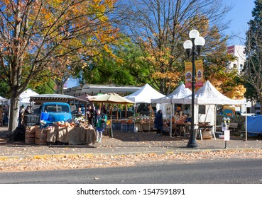 Eugene, OR, 10/29/19: Farmers market customers and vendors mingle with produce and old truck on display on a sunny fall day in downtown