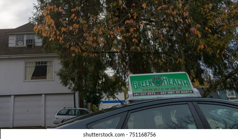 EUGENE, OREGON NOVEMBER 7, 2017 Marijuana delivery vehicle top on the street with trees and buildings. Marijuana delivery rolls out in Eugene, following a trend started in Vancouver BC