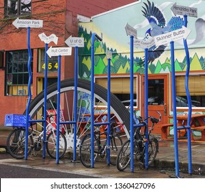 Eugene, Oregon USA - March 23, 2019: Bicycle stand with direction signs, times and distances to local landmarks and places of interest on 5th Street in downtown.
