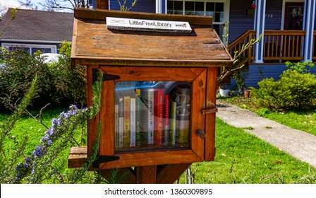 Eugene, Oregon USA - March 31, 2019: A wooden Little Free Library box in a neighborhood yard is full of books available to passers-by