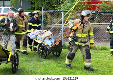 Eugene, Oregon, USA Â?Â? May 2, 2012: Eugene, OR Emergency Services and National Guard work in a disaster response drill. The unidentified firemen are transporting unidentified injured to landing zone.