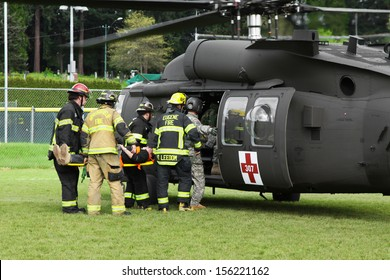 Eugene, Oregon, USA Â?Â? May 2, 2012: In Eugene, OR local Emergency Services and National Guard work together in a disaster response drill. Unidentified firemen carry an injured person to the helicopter.