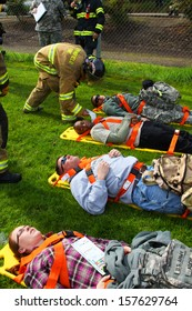 EUGENE, OREGON USA Â?Â? May 2, 2012: Eugene, OR the local Emergency Services and National Guard work together in a disaster drill. The firemen are reviewing the injury status cards on the injured.
