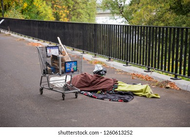Eugene, OR - September 22, 2018: Anonymous homeless person sleeping on the streets of Eugene Oregon covered in blankets with a shopping cart for personal belongings.