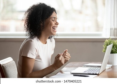 Euphoric happy african american young woman sitting at table with computer, received good news email, celebrating important business achievement, online lottery win, got high paid dream job offer.