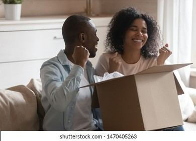 Euphoric happy millennial african american family couple sitting on couch in living room, holding long awaited cardboard box parcel from online store or winner prize, unpacking together at home.