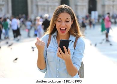 Euphoric happy winner woman watching very good news on her smart phone in square