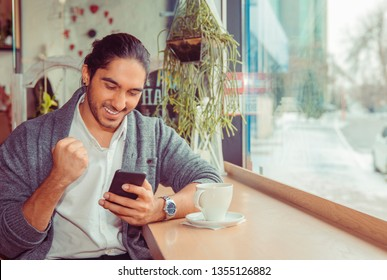 Euphoric man pumping fist while looking at mobile smartphone. Portrait of a handsome guy wearing formal wear sitting near window at a table in living room or coffee shop. Mixed race indian and turkish