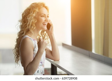 Euphoric woman searching job in cafe. Beautiful girl is talking on the phone and happy with the good news. sunlight, copy space