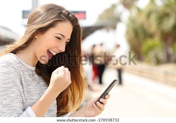 Mujer eufórica viendo su smartphone en una estación de tren mientras espera