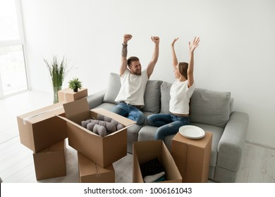 Euphoric young couple feeling happy about moving in new home with boxes, celebrating relocation into own apartment, excited man and woman house owners raising hands proud with buying real estate