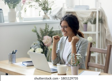 Euphoric young creative designer looking at laptop screen, celebrating receiving good news at modern showroom. Emotional happy businesswoman in glasses getting bank loan approval or making first sake.