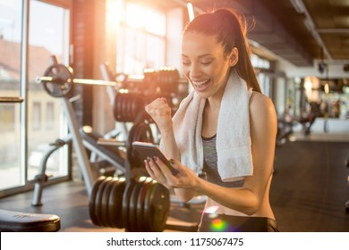 Euphoric young fit woman cheering at good news on her mobile phone and punching the air with her fist while relaxing in gym