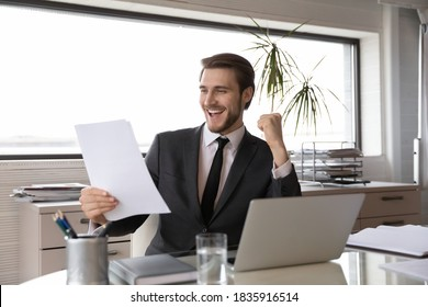 Euphoric young happy businessman in suit reading paper letter with good news, celebrating professional achievement, unbelievable company growth corporate success or profitable deal in office.