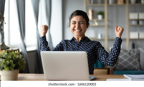 Euphoric young indian girl student winner celebrate victory triumph sit at home desk with laptop computer win online fortune feel excited get new job opportunity good exam result great news concept