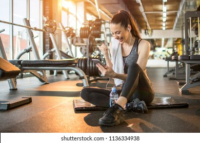 Euphoric young woman reading good news on mobile phone during rest in fitness workout at gym