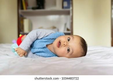 Eurasian baby lying on bed