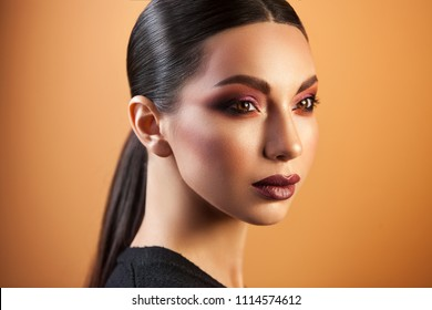 a Eurasian girl with sleek hair staring into the distance on an orange background, graceful make-up gleams her eyes and sensual lips.