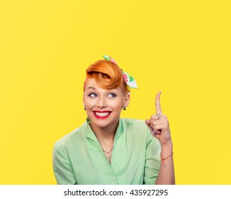 Eureka. Closeup portrait happy friendly young woman showing index finger isolated yellow background wall. Pinup girl retro vintage 50's hairstyle. Positive human face expressions emotions feelings