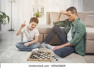 Eureka. Excited boy is pointing finger up while looking at checkers on board with joy. Man is sitting on floor and expressing desperation. Victory concept