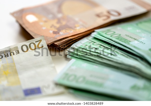 Euro banknotes arranged in a pile. A large amount of money with a shallow depth of field.
