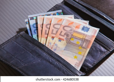euro banknotes in brown leather purse