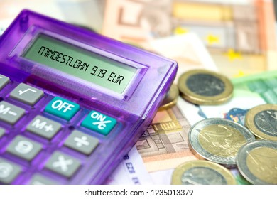 Euro banknotes, calculator and German translation for minimum wage 9,19 EUR