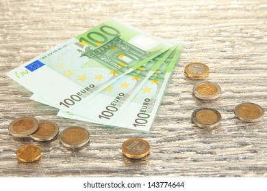 Euro banknotes and euro cents on grey glass background