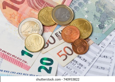 Euro banknotes and coins with bills to pay. Selected focus, narrow depth of field.