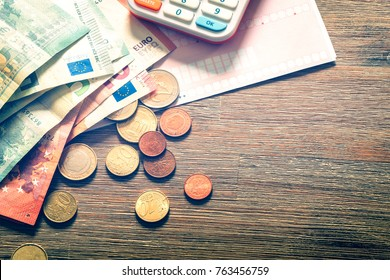 Euro banknotes and coins with bills to pay. Finance concept