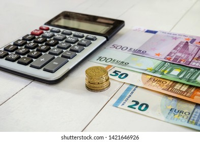 euro banknotes, coins and calculator on white table