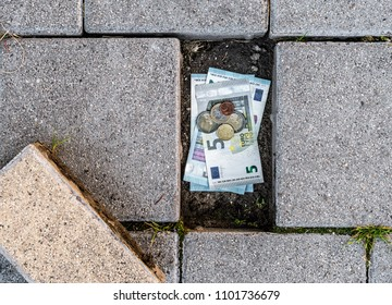Euro banknotes and coins found under a loose pavement brick. Concept of poverty and running out of personal savings