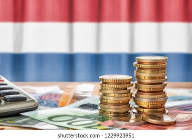 Euro banknotes and coins in front of the national flag of the Netherlands