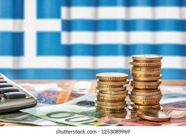 Euro banknotes and coins in front of the national flag of Greece