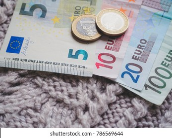 Euro banknotes and coins on knitted sweater. Winter time.