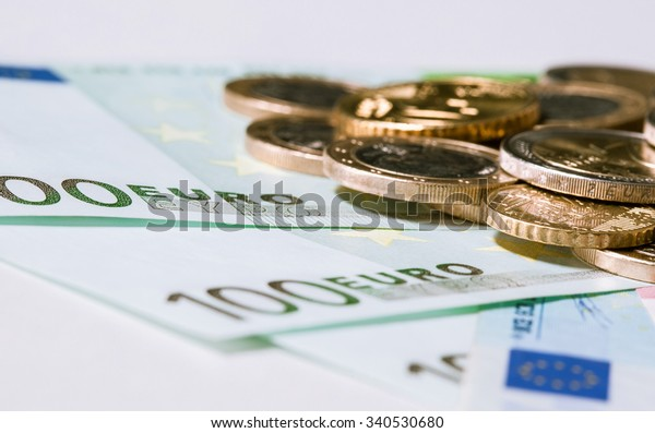 Euro banknotes and coins on neutral background