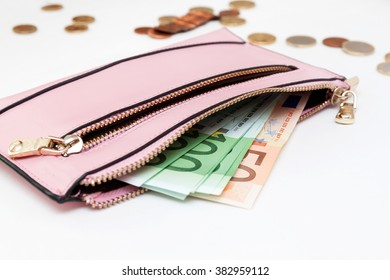 Euro banknotes and coins in wallet on white background