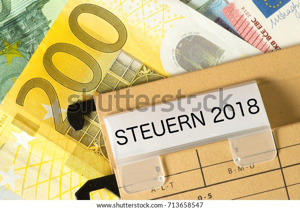 Euro banknotes and a folder with the print taxes 2018 in German