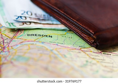 Euro banknotes inside wallet on a geographical map of Dresden, Germany