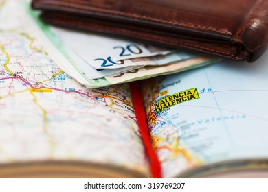 Euro banknotes inside wallet on a geographical map of Valencia, Spain