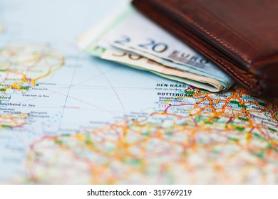 Euro banknotes inside wallet on a geographical map of Rotterdam, Netherlands