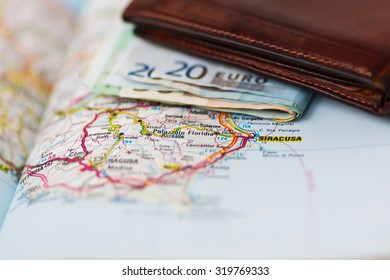 Euro banknotes inside wallet on a geographical map of Siracusa, Italy