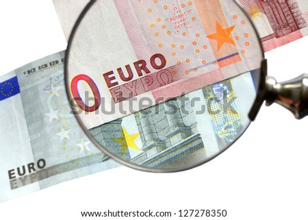 Euro banknotes and magnifying glass, isolated on white.